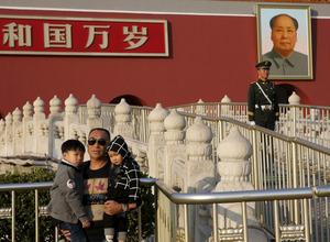 北京の天安門に掲げられた毛沢東の肖像画の前で、子どもたちを抱いて写真を撮る男性=ロイター