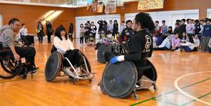 小学生が車いすラグビーのタックルを体験。歓声も上がった=横浜市青葉区黒須田