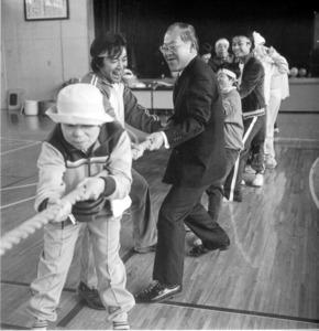 本に掲載された写真の1コマ。背広姿の河合洋祐さんが、ふれあいの里どんぐりの仲間たちと綱引きに興じる=豆塚猛さん撮影