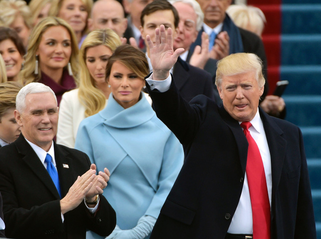 20日、ワシントンの米議会議事堂前の就任式の会場に到着し、群衆に手を振るトランプ新大統領(右)。中央はメラニア夫人、左端はペンス新副大統領=AFP時事