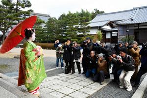 舞妓の佳つ花さんを撮影する参加者ら=東山区