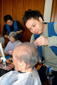 利用者の髪を切る美容師の湯浅一也さん(右)と桜庭太さん=世田谷区