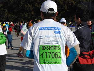 背中上部に注意喚起のメッセージが書かれたTシャツを着て走る捜査員=千葉市美浜区