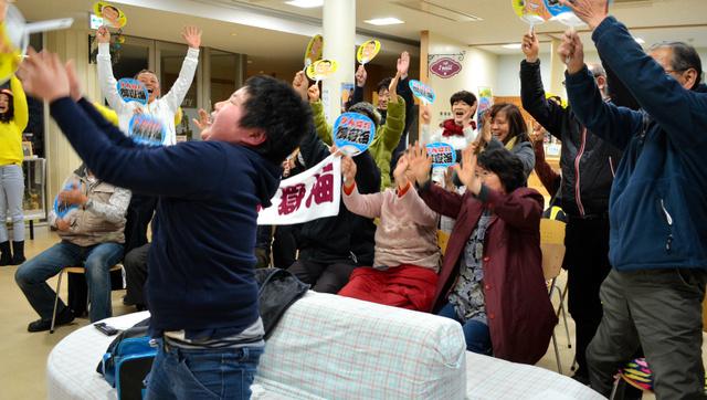 御嶽海が千秋楽を白星で締めくくり、立ち上がって万歳を繰り返す熱心な地元ファンら=上松町公民館