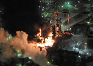 黒い煙を上げて燃えるコンビナート=22日午後5時55分、和歌山県有田市、朝日新聞社ヘリから、伊藤進之介撮影
