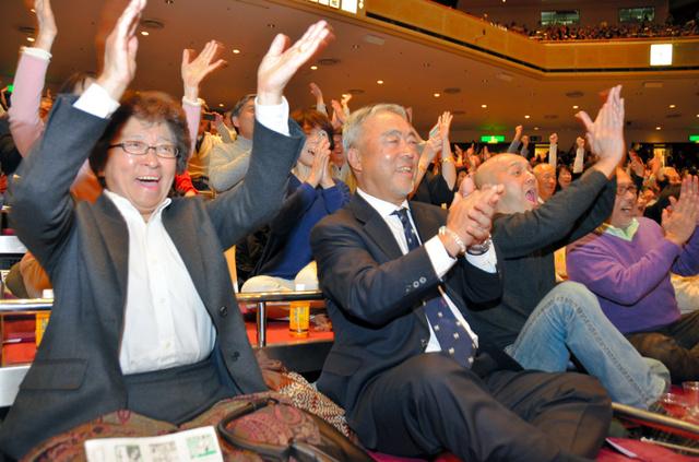 稀勢の里が白鵬を破り、手をたたいて喜ぶ父親の萩原貞彦さん(手前右)と母親の裕美子さん(同左)=22日、東京・国技館