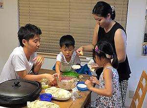 昨年8月の「育ボスブートキャンプ」で、社員の子どもたちとギョーザ作りをする池田脩太郎さん(左)。管理職の女性と2人で訪問した=リクルートマーケティングパートナーズ提供