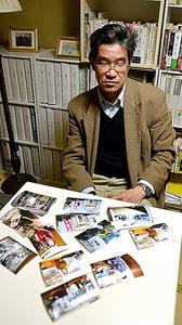 聞き取り活動をする中で撮った写真を見る元職員の西角純志さん=昨年12月、東京都八王子市