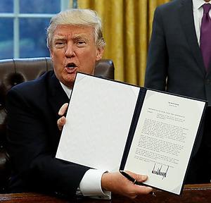 ホワイトハウスで23日、署名したTPPから離脱するための大統領令を見せるトランプ氏=ロイター