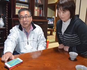 携帯電話に送られてきたレースの動画を見る父の渡辺謙司さんと母成子さん=津久見市