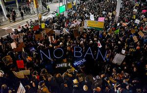 ニューヨークのケネディ空港で28日、移民の入国を制限する大統領令に抗議デモを行う人たち=AFP時事