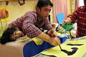 職員の佐藤悦也さんの手を借りて、新年を祝う数字を毛筆で書く高橋清文さん(下)=横浜市栄区