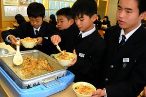ギンザケの中骨レトルト品を使った混ぜ込みご飯をいっぱいに盛る生徒=山形県高畠町の高畠中
