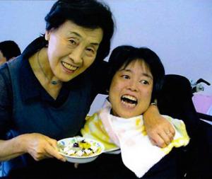 伊藤光子さんと次女のまゆみさん。提供を受けた7枚の写真はすべて、まゆみさんの肩を抱く光子さんの姿が写っていた。「やっぱり、母親ですからね。常にまゆみを感じていたいんです」