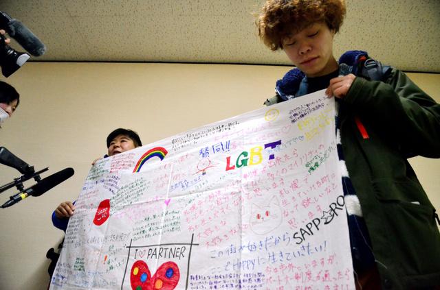 パートナーシップ制度の創設を求めるLGBTの人たちのメッセージが書かれた旗を広げ、喜びを語る傍聴者ら=札幌市議会