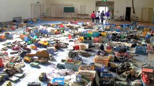 「『長面』きえた故郷」の一場面。震災直後に遺体が安置された体育館は、やがてがれきの中から出てきた品々が置かれるようになった=石原牧子さん提供