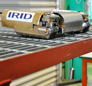 福島第一原発1号機の格納容器内に投入される調査ロボット。カメラと線量計、照明が一体になった計測ユニットを垂らして計測する=茨城県日立市