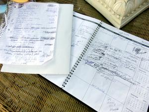 ぎっしりと予定が書かれているトムさんのノートとカレンダー。約束や予定の変更はすぐに書き込む