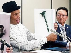 折れたポールの写真を持ち、話すレイモンド・ジョンソンさん(左)=東京・霞が関