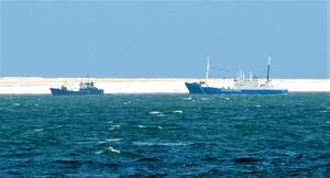 歯舞群島・水晶島付近にいたロシアの巡視船(右)と貨物船。望遠レンズでのぞくと、巡視船の船体に書かれた文字が見える距離だ=北海道・納沙布岬沖の珸瑤瑁(ごようまい)水道、神村正史撮影
