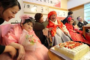 ピンク色のドレスを着て出席した岩坂すえ子さん(左から2人目)ら=水俣市浜町1丁目の「ほっとはうす」
