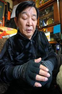 阪神・淡路大震災で家具の下敷きになり脊髄などを損傷した野田正吉さん。手のしびれを和らげるため夏でも手袋をつけるという=兵庫県西宮市