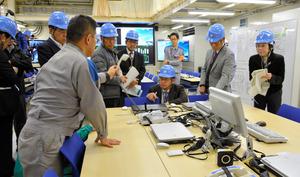 代替緊急時対策所で、緊急時に使われる通信機器について説明を受ける専門委の委員たち=薩摩川内市