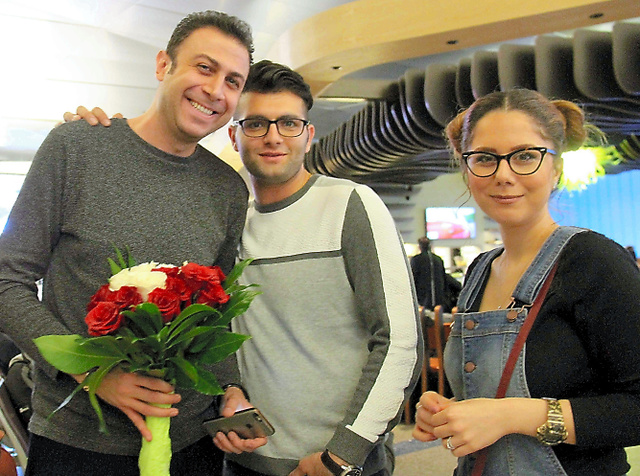 ロサンゼルス国際空港で友人たちに花束で迎えられたイラン人男性のペヘルーズさん(左)=いずれも5日、ロサンゼルス、平山亜理撮影
