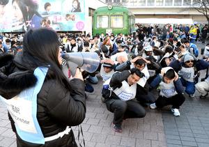 渋谷駅前での訓練で、通訳(左)からの指示を受けて身の安全を守る姿勢をとる外国人たち=渋谷区