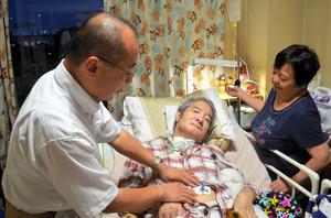 患者の胃ろうチューブを交換する赤羽重樹医師(左)と様子を見守る妻。1カ月~半年ごとに交換が必要という=横浜市神奈川区
