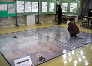 県立図書館の床に広げられた鹿児島城下の古地図=鹿児島市
