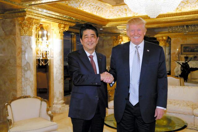 トランプ氏(右)と会談し、握手する安倍晋三首相=2016年11月17日、米ニューヨーク、内閣広報室提供