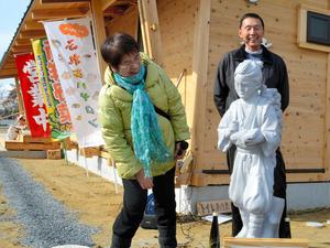 修復した二宮金次郎像を見つめる本間英一さん(奥)と鈴木洋子さん=石巻市門脇町2丁目