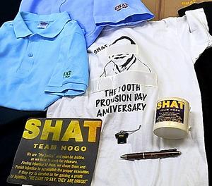 SHATの文字が入ったTシャツ、マウスパッド、マグカップ、ボールペンなど。職員の似顔絵にはテープが貼られている=9日午後3時45分、神奈川県小田原市荻窪の小田原市役所、村野英一撮影