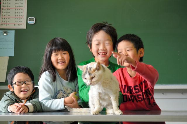 昨年11月、たまを観察し、絵と文章で伝える授業があり、笑顔でたまを囲む1年生の児童たち(長野県伊那市立新山小学校提供)