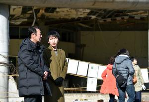 大川小の旧校舎前で語り合う佐々木奏太さん(右)と佐藤和隆さん。後方は奏太さんの父親が担任をしていた2年生の教室=5日、宮城県石巻市釜谷、福留庸友撮影