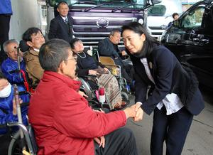到着した石川さゆりさんを出迎え、握手を交わす「若かった患者の会」の滝下昌文さん=水俣市