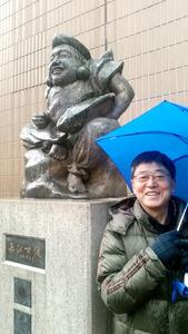 この日は冷たい雨が降っていたが、伊郷俊行さんは笑顔で迎えてくれた。後方は「えびす像」=東京都渋谷区