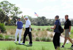 米フロリダ州・パームビーチでゴルフを楽しみ、ハイタッチをする安倍晋三首相(左)とトランプ大統領(左から2番目)=11日、内閣広報室提供