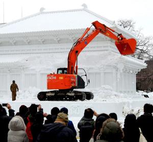 さっぽろ雪まつりの閉幕から一夜明け、「興福寺中金堂」の解体作業を多くの人が見守った=札幌市中央区、山本裕之撮影