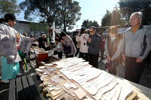 仮の拝殿を前に手や足の形をした絵馬を捧げ、大勢の人たちが手を合わせた=15日午前10時37分、熊本県嘉島町の甲斐神社、小宮路勝撮影