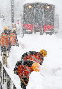 JR青谷(あおや)駅を出て約300メートル進んだところで動けなくなった列車。除雪作業が進められた=11日、鳥取市青谷町