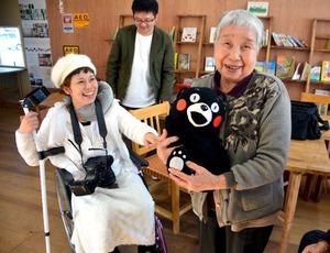 車いすで撮影に訪れた柳田かおりさん(左)。その笑顔と明るい声に、被災者の表情もほころんだ=熊本県西原村、平井良和撮影