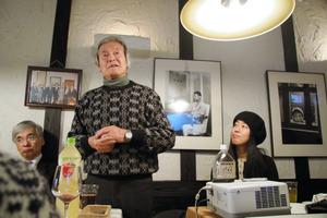 故・川本輝夫さんの写真の前で思い出を語る元水俣市長の吉井正澄さん(中央)=水俣市