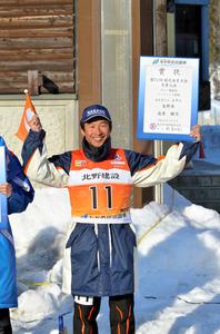 8位入賞の賞状を掲げ、笑顔を見せる荻原健司選手=長野県白馬村神城、白馬クロスカントリー競技場