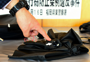 小さな穴が開けられた折りたたみ傘。盗撮用のカメラとライトが仕込まれていた=16日午後2時57分、福岡市東区の福岡県警東署、宮谷由枝撮影