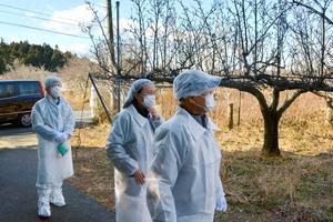 鎌田清衛さん(右端)のナシ園を見る柳美里さん(右から2人目)と青来有一さん(左端)=福島県大熊町