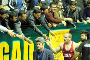 イラン人観衆と手を合わせる米国のデビッド・テイラー選手=16日、イラン西部ケルマンシャー、神田大介撮影