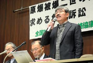 提訴後、集団訴訟の意義を語る原告団長の崎山昇さん=広島市中区