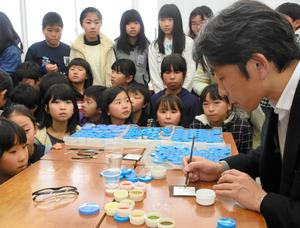 銅に上薬をつける作業を見つめる児童=廿日市市